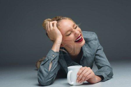 Photo pour Belle fille riante avec tasse de café couché sur gris - image libre de droit