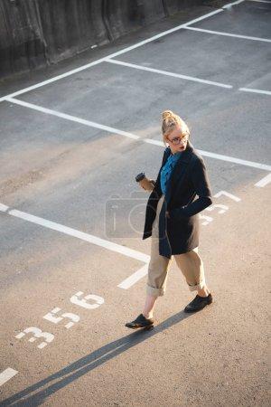 schöne stilvolle Mädchen mit Kaffee zu Fuß auf dem Parkplatz