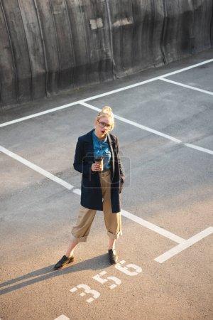 Stylische junge Frau mit Coffee to go posiert auf dem Parkplatz