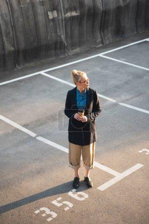 attraktive modische Mädchen mit Kaffee to go auf dem Parkplatz stehen