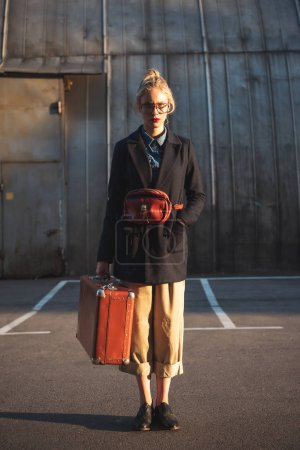 attractive fashionable girl with waist bag holding vintage suitcase on urban parking