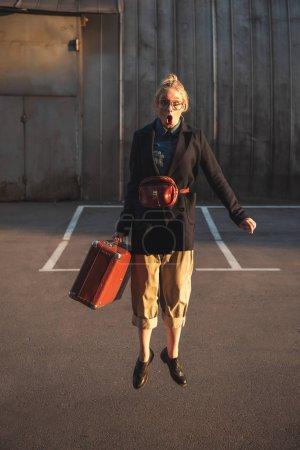 stylish shocked girl jumping with vintage suitcase on urban parking