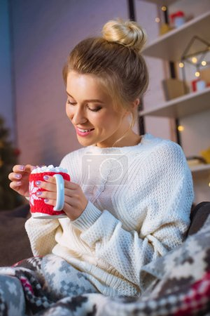 smiling young blonde woman covered in blanket sitting on couch and holding cup of hot cocoa with marshmallows at christmas time