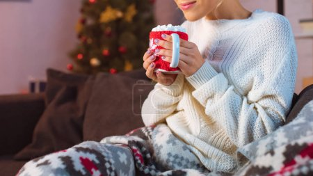 cropped view of young woman covered in blanket sitting on couch and holding cup of hot cocoa with marshmallows at christmas time