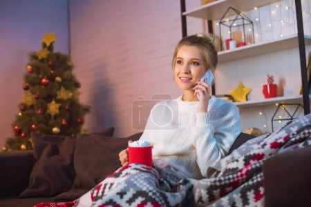Photo for Young blonde woman covered in blanket sitting on couch, holding cup of hot cocoa with marshmallows and talking on smartphone at christmas time - Royalty Free Image