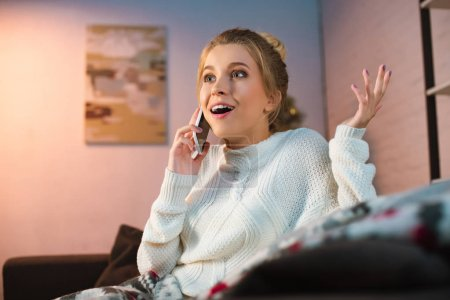 excited young blonde woman talking on smartphone at christmas time