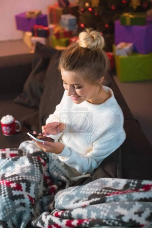 smiling young blonde woman sitting on couch and using smartphone at christmas time