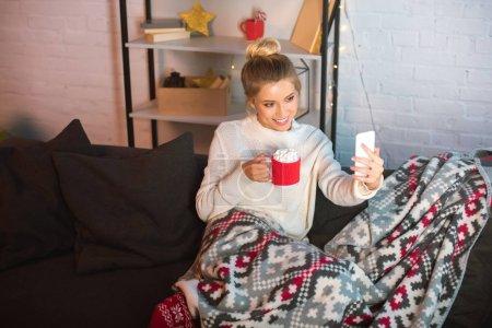 Photo pour Jeune femme blonde heureuse couverts dans couverture assis sur le canapé, tenant la tasse de chocolat chaud avec des guimauves et prenant selfie sur smartphone au moment de Noël - image libre de droit