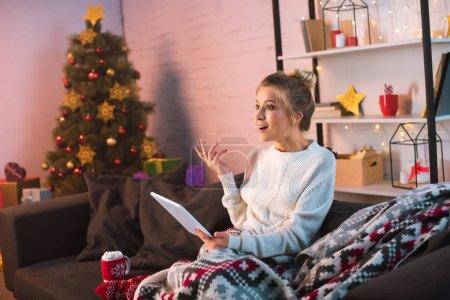 Photo pour Excitée jeune femme blonde assise sur le canapé et en utilisant une tablette à Noël - image libre de droit
