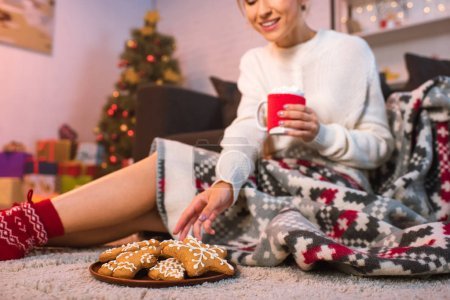 woman in patterned blanked holding christmas gingerbread cookies and cocoa
