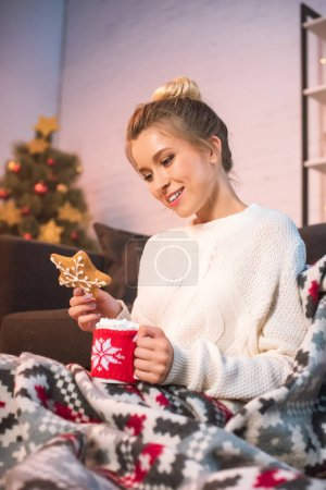 woman in blanked holding christmas gingerbread cookie and cup with hot cocoa