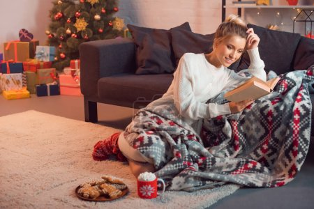 Charming girl smiling and reading book at home on Christmas eve