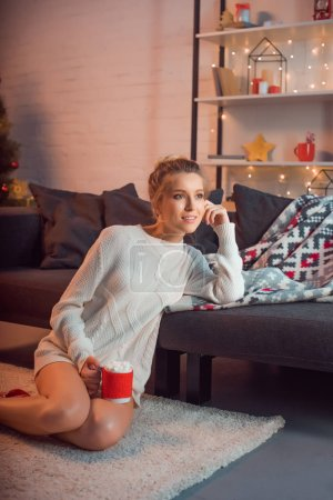 beautiful woman sitting in christmas patterned socks on carpet with mug of cocoa