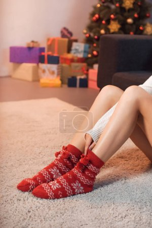 woman in christmas patterned socks sitting on carpet