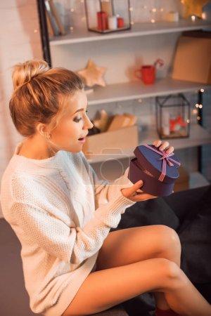 überraschte junge Frau sitzt auf Sofa und öffnet Weihnachtsgeschenk