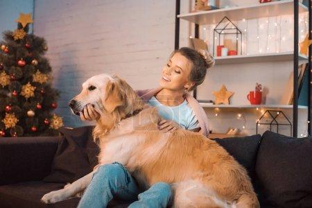 Photo pour Belle femme blonde jeune heureuse assis sur le canapé et étreindre chien golden retriever au moment de Noël - image libre de droit