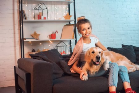 Photo for Beautiful young blonde woman sitting on couch, hugging golden retriever dog, smiling and looking at camera - Royalty Free Image