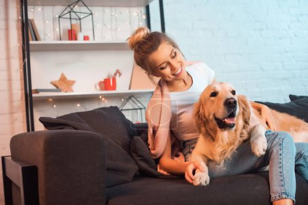 Photo for Beautiful smiling young blonde woman sitting on couch and hugging golden retriever dog at christmas time - Royalty Free Image