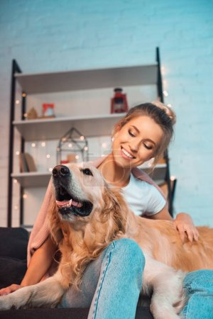 Photo for Beautiful cheerful young blonde woman sitting on couch and hugging golden retriever dog at christmas time - Royalty Free Image