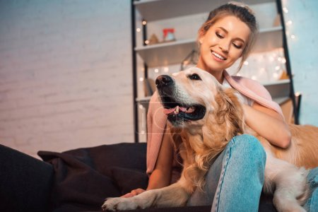 Photo for Beautiful happy young blonde woman sitting on couch and hugging golden retriever dog at christmas time - Royalty Free Image