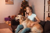 beautiful young blonde woman sitting on couch with golden retriever dog and talking on smartphone at christmas time