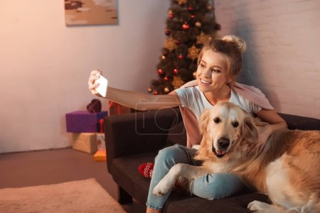 Photo for Beautiful young blonde woman sitting on couch with golden retriever dog and taking selfie on smartphone at christmas time - Royalty Free Image