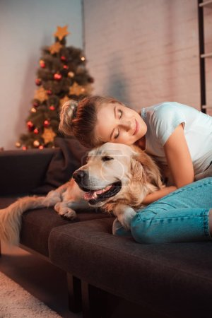 Photo for Beautiful smiling young blonde woman on couch hugging golden retriever dog at christmas time - Royalty Free Image