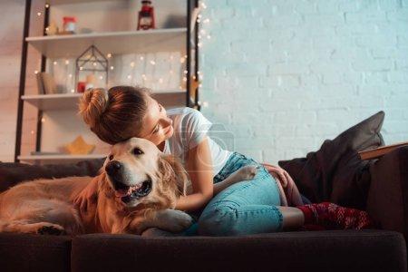 Photo pour Jeune femme blonde sur canapé étreindre chien golden retriever au moment de Noël - image libre de droit