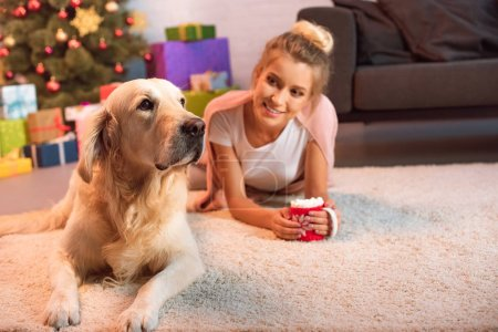 Photo for Beautiful young blonde woman lying on fluffy rug with golden retriever dog and cup of hot cocoa with marshmallows at christmas time - Royalty Free Image