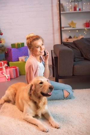 Photo for Beautiful young blonde woman sitting on floor with golden retriever dog and talking on smartphone at christmas time - Royalty Free Image