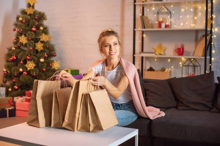 smiling young blonde woman sitting on couch with shopping bags at christmas time