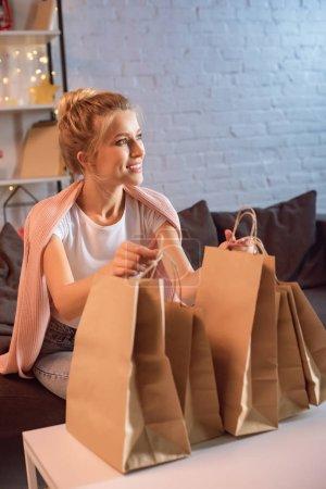 Foto de Feliz joven mujer rubia sentada en sofá con bolsas de compras en Navidad - Imagen libre de derechos