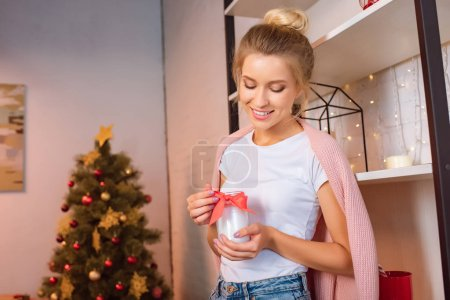 smiling young blonde woman holding candle with red ribbon at christmas time