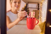 smiling young blonde woman putting candy canes in red cup at christmas time