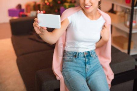 Photo pour Vue recadrée souriante jeune femme assise sur le canapé et prise selfie sur smartphone au moment de Noël - image libre de droit