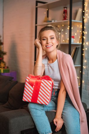 happy young blonde woman sitting on couch with present and looking at camera at christmas time
