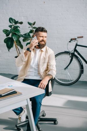 Photo for Bearded businessman sitting in office chair and talking on smartphone - Royalty Free Image