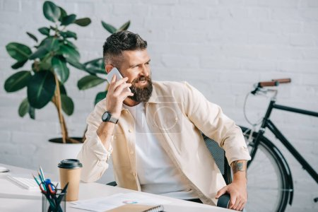 Photo for Successful businessman sitting in office and talking on smartphone - Royalty Free Image