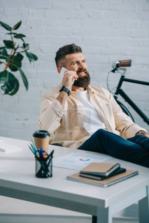 Photo for Smiling bearded businessman sitting in modern office and talking on smartphone - Royalty Free Image