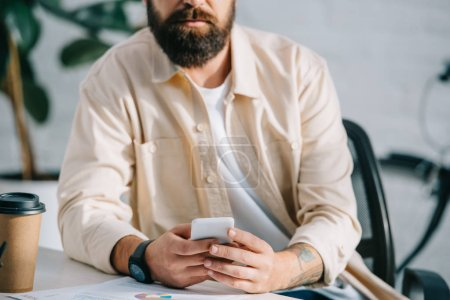 Cropped view of bearded man sitting in office and holding smartphone