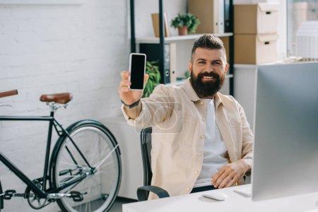 Photo pour Homme d'affaires souriant montrant le smartphone à la caméra - image libre de droit