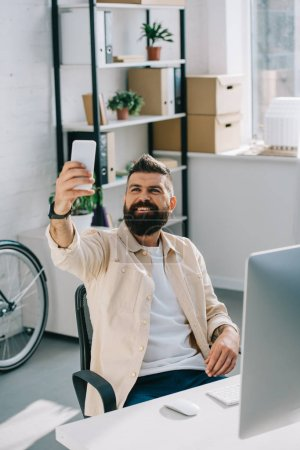 Smiling bearded businessman taking selfie while sitting in office chair