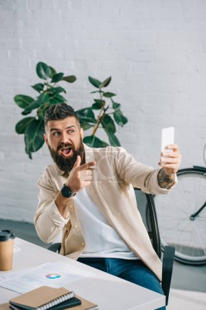 Photo for Bearded businessman taking selfie on smartphone and gesturing in modern office - Royalty Free Image