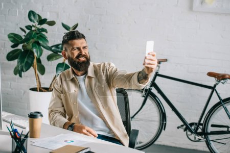successful businessman laughing and taking selfie in office chair