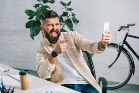 Photo for Bearded businessman pointing at camera while taking selfie in office chair - Royalty Free Image