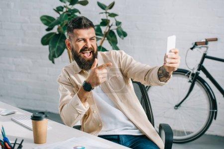 Photo pour Homme d'affaires barbu, pointant à la caméra tout en profitant de selfie de chaise de bureau - image libre de droit