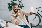 Bearded businessman pointing at camera while taking selfie in office chair