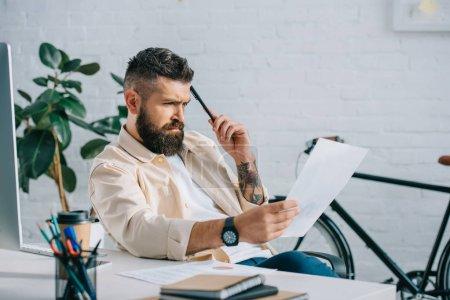 Photo pour Homme d'affaires grave, lecture des documents au bureau dans le bureau moderne - image libre de droit