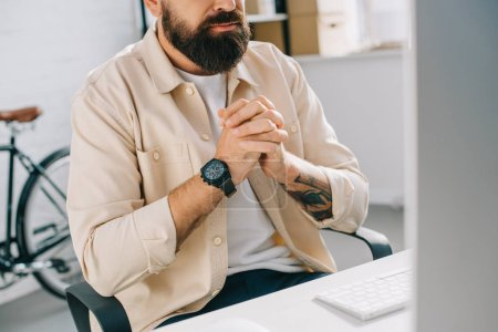 Cropped view of bearded businessman with clenched hands sitting at computer desk
