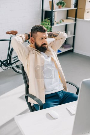 Bearded businessman sitting in office chair and putting hands behind head